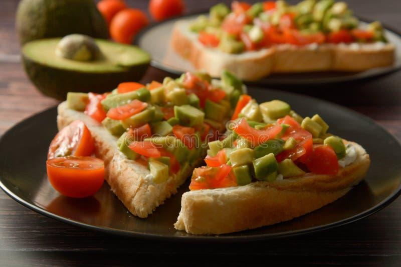 Sunt rostat bröd med avokadot, körsbärsröda tomater och ost på en platta table tr? royaltyfri fotografi