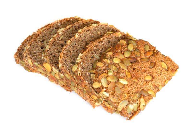 Sunt skivat bröd med pumpa kärnar ur isolerat på en vit bakgrund Brödskivor och smulor som beskådas från över fotografering för bildbyråer