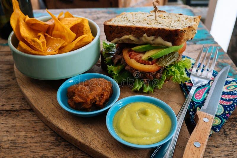 sunt snabbmat hamburgare med en kotlett, grönsallat med sötpotatissmåfiskar och två såser Smaklig smörgås för lunch på arkivfoto