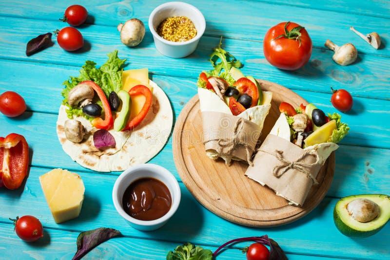 Sunt strikt vegetarianlunchmellanmål Tortillasjalar med champinjoner, nya grönsaker och ingredienser på blå träbakgrund royaltyfria bilder