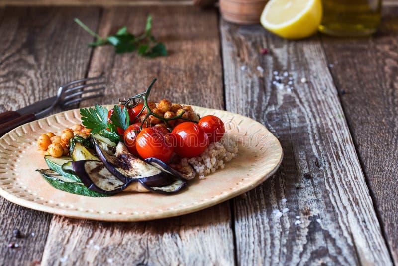 Sunt strikt vegetarianmål, grillade körsbärsröda tomater, aubergine, zucchini, quinoa, grillade kikärtar fotografering för bildbyråer