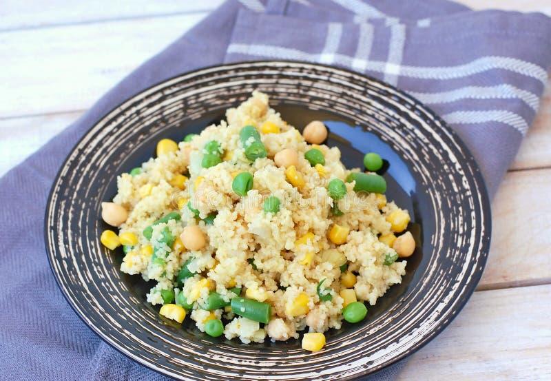Sunt strikt vegetarianmål med hel korncouscous, kikärtar, majs, ärtor, haricot vert på den mörka plattan på den gråa torkduken på arkivfoto
