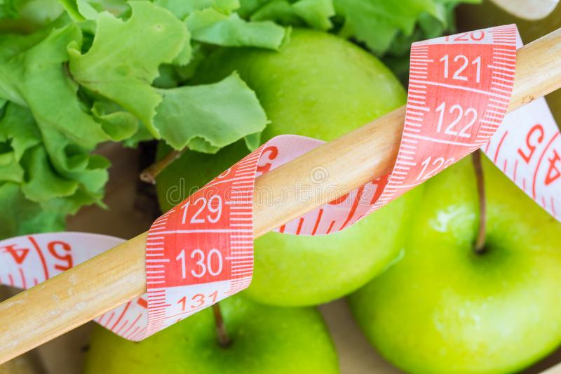 Sunt ?ta och banta begrepp Stäng sig upp av att mäta bandet med gröna äpplen och grön ekgrönsallat i den gjorda suddig träkorgen royaltyfria foton