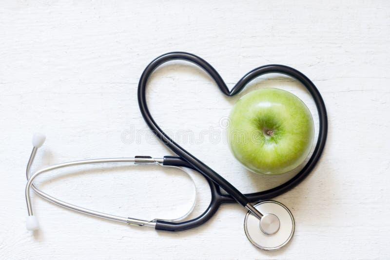 Sunt teckenbegrepp för alternativ medicin med stetoskophjärta och gräsplanäpplet på vit bakgrund arkivfoto
