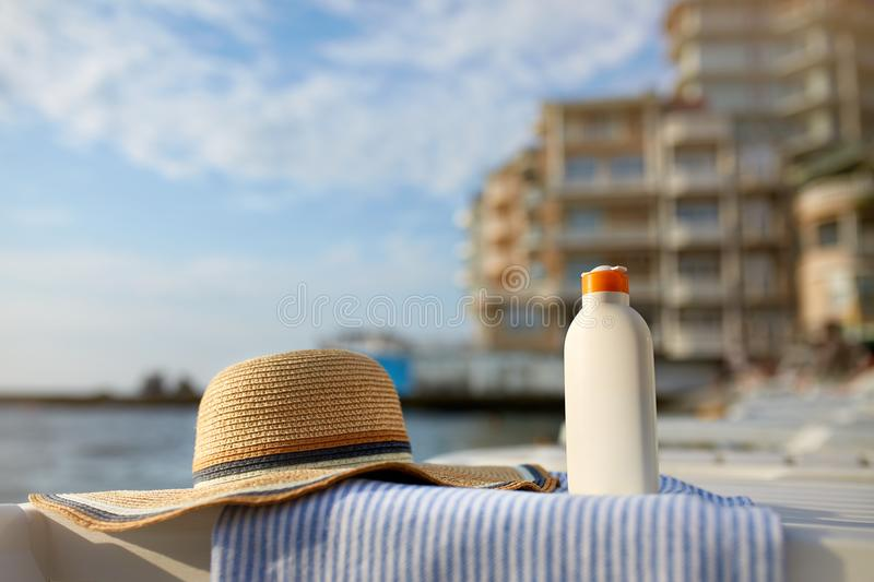 Suntan cream bottle on beach towel with sea shore on background. Sunscreen on deck chair outdoors on sunrise or sunset. At luxury spa resort. Skin care and stock photo