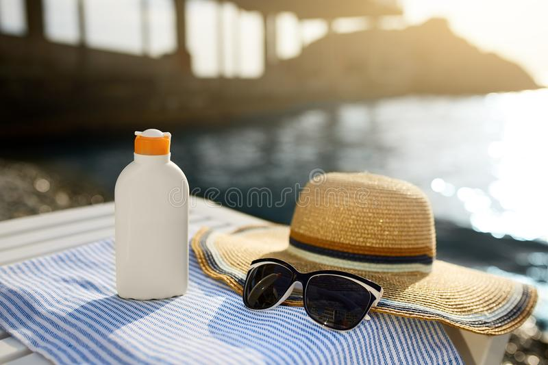 Suntan cream bottle and sunglasses on beach towel with sea shore on background. Sunscreen on deck chair outdoors on. Sunrise or sunset. Skin care and protection stock photography