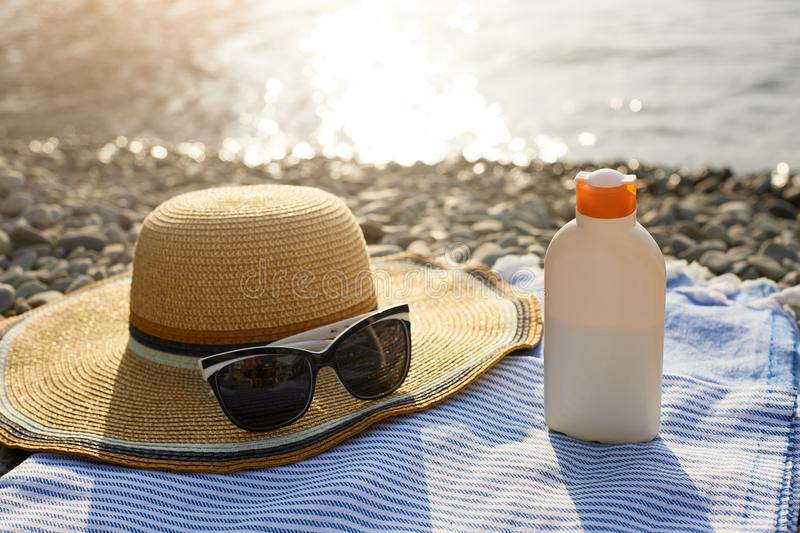 Suntan cream bottle and sunglasses on beach towel with sea shore on background. Sunscreen on deck chair outdoors on. Sunrise or sunset. Skin care and protection royalty free stock image