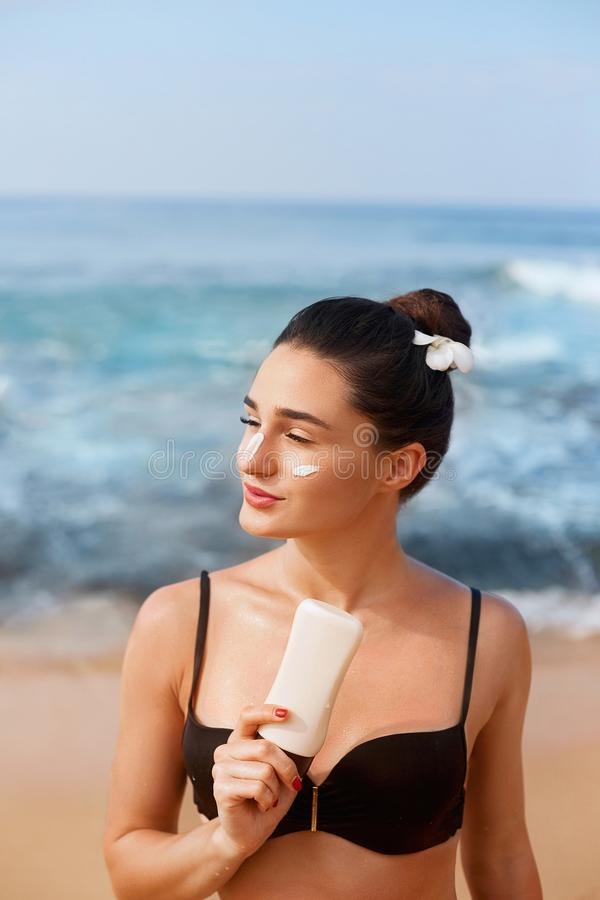 Suntan Lotion. Sexy Young Woman Applying Sunscreen Solar Cream on the beach.Sun Protection. Sun Cream. Skin and Body Care.Girl Hol stock image