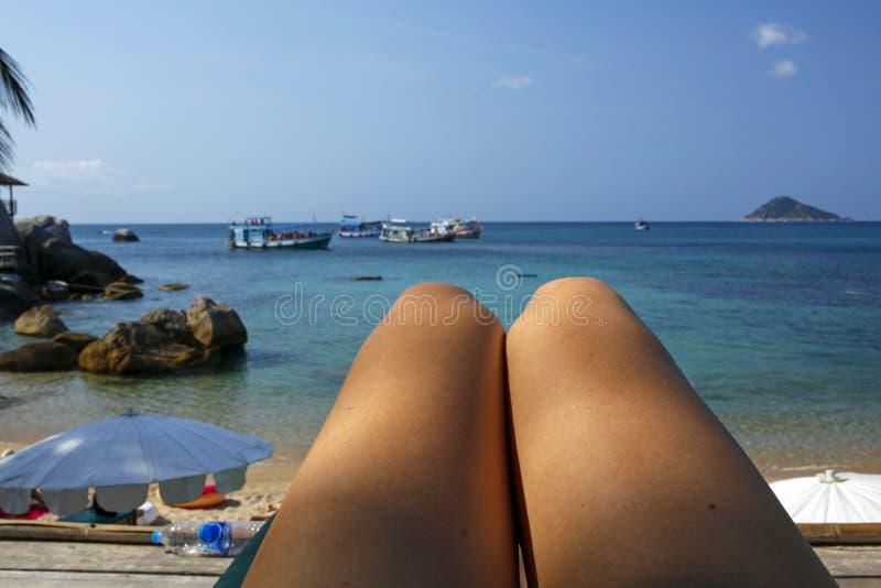 Suntanned żeńskie nogi przeciw raj plaży zdjęcie stock