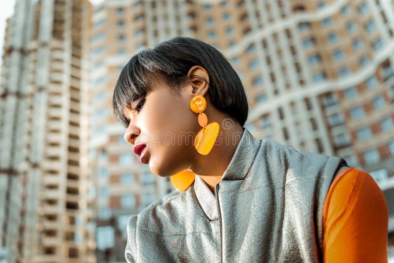 Suntanned безупречная женщина accenting внимание к ее оранжевым серьгам стоковое фото rf