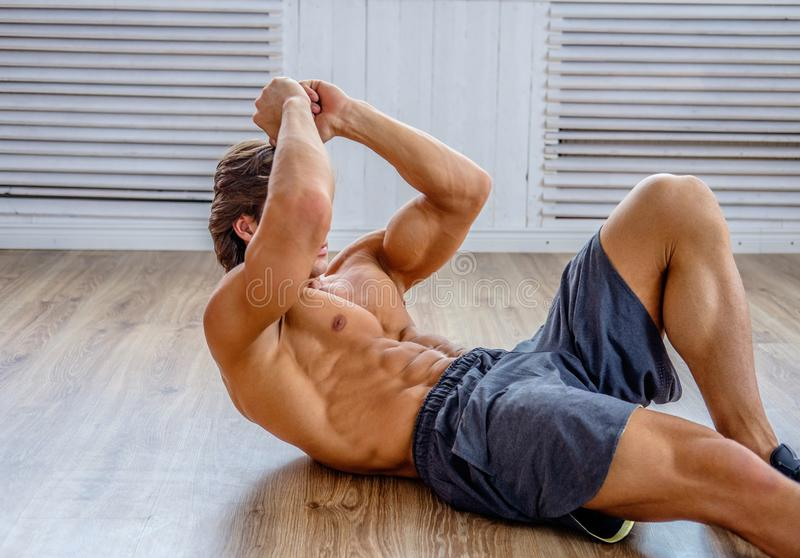 Suntanned athletic male doing stomach workouts. Suntanned athletic male doing stomach workouts on the floor in natural soft light royalty free stock photos