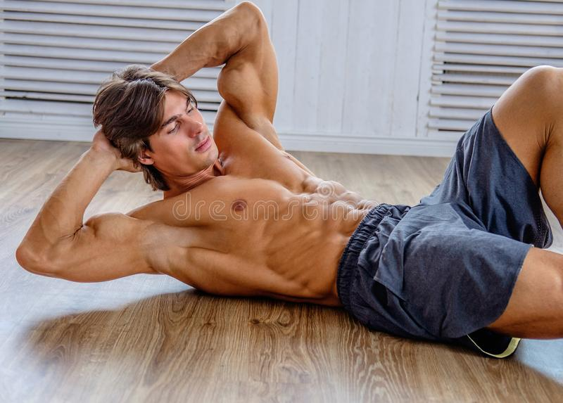 Suntanned athletic male doing stomach workouts. Suntanned athletic male doing stomach workouts on the floor in natural soft light royalty free stock images