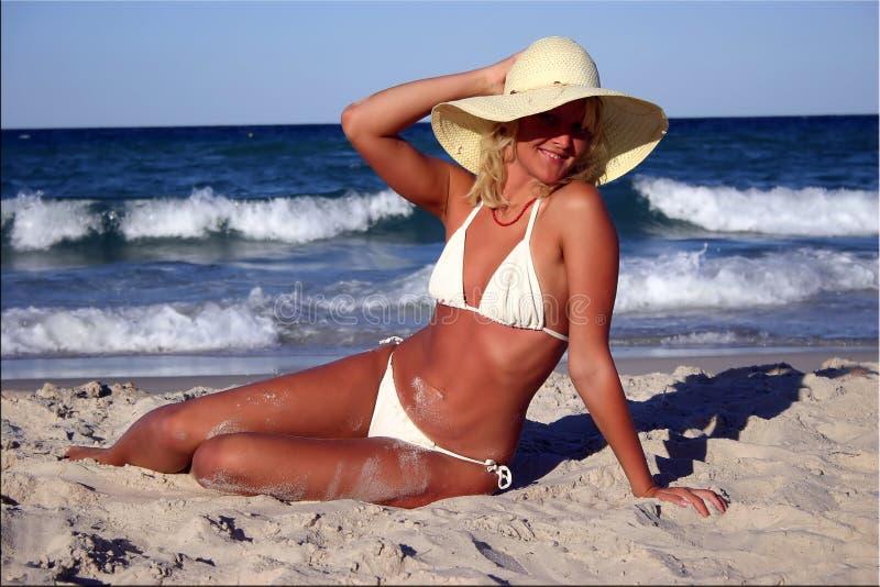 Suntanned blonde in bikini. Smilimg beautiful suntanned blonde in white bikini & straw on the sand near the sea royalty free stock photography