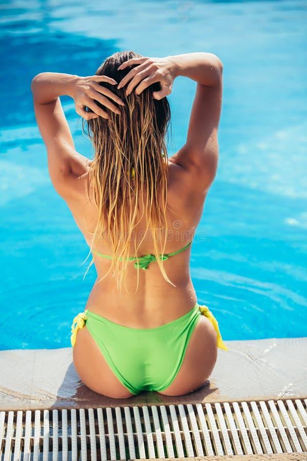 Suntanned junge Frau, die nahe Swimmingpool sich entspannt lizenzfreie stockfotografie