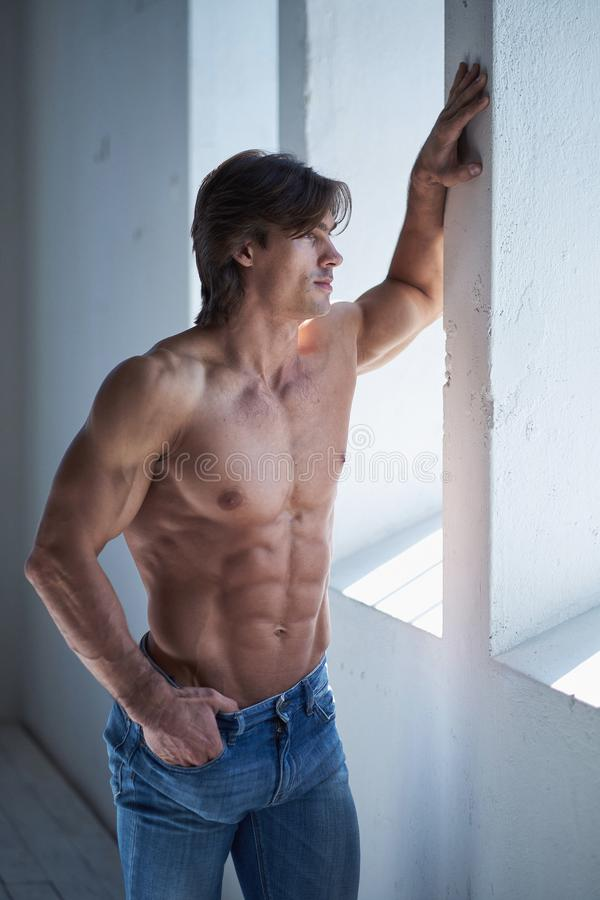 Portrait of suntanned muscular guy in denim jeans. Suntanned muscular male in blue jeans posing in natural light from window stock photography