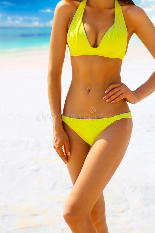 Suntanned woman body in yellow swimsuit against the beach.  stock photography