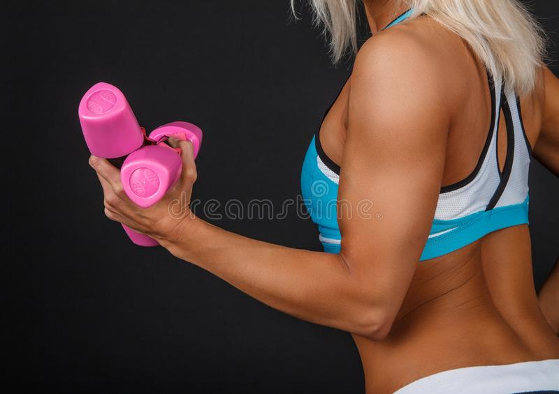 Suntanned woman`s arm with pair of pink dumbbells. Suntanned woman`s arm with pair of pink dumbbells on black background royalty free stock image