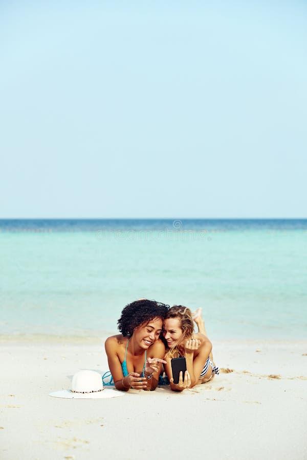 2 suntanning друз смотря фото мобильного телефона на пляже стоковые фото