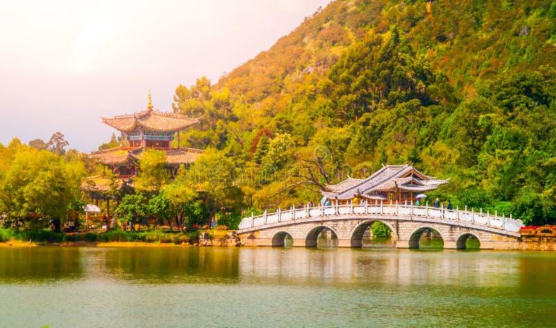 Suocui bro över svarta Dragon Pool på månen som omfamnar paviljongen i Jade Spring Park, Lijiang, Kina royaltyfri fotografi