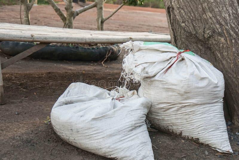 Suolo e fertilizzante nelle borse bianche del sacco fotografie stock