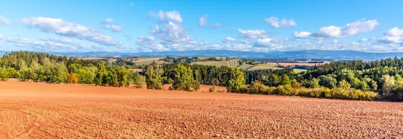 Suolo rosso tipico della campagna intorno a Nova Paka Paesaggio agricolo con le montagne giganti sui precedenti ceco fotografie stock libere da diritti