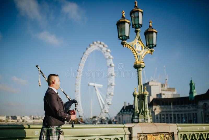 Suonatore di cornamusa che gioca musica scozzese in ponte di Westminster, con London Eye nei precedenti immagini stock