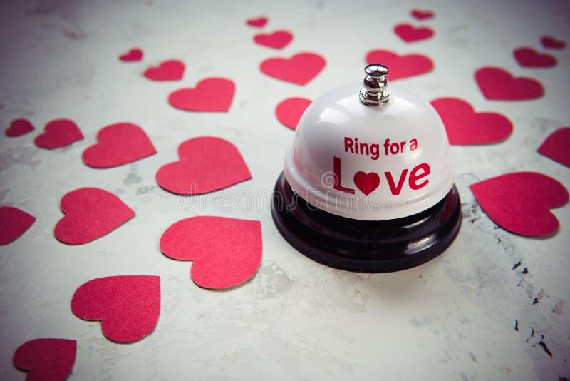 Suoni la campana per un amore e molti cuori su un fondo di legno fotografia stock libera da diritti