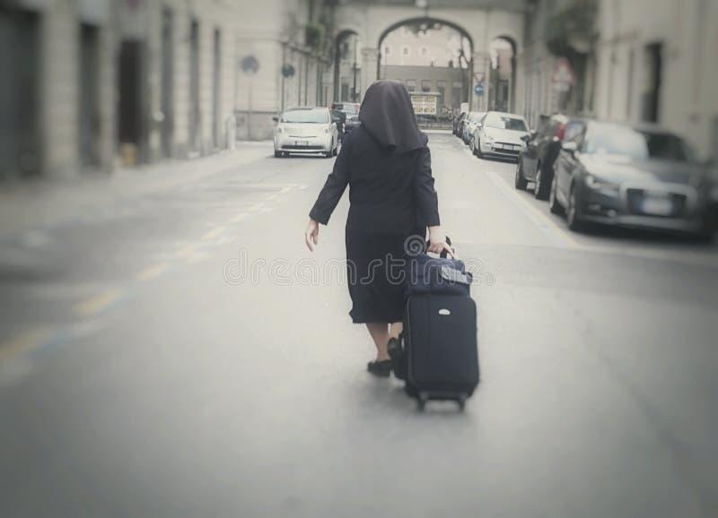 Suora che tiene bagagli sulla strada immagini stock libere da diritti