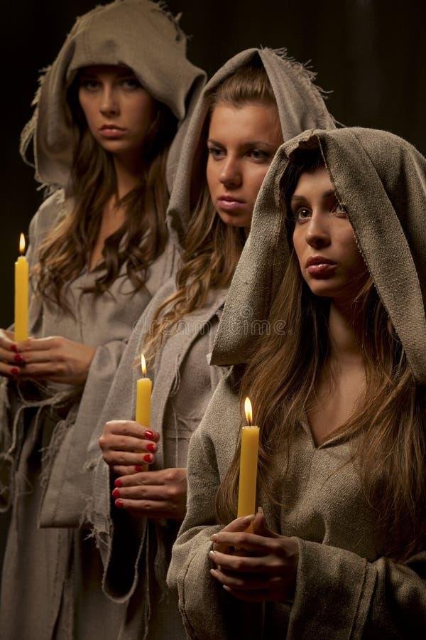 Suore che praing con le candele fotografia stock libera da diritti