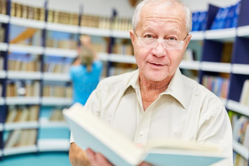 Supérieur dans la bibliothèque dans la maison de retraite photographie stock