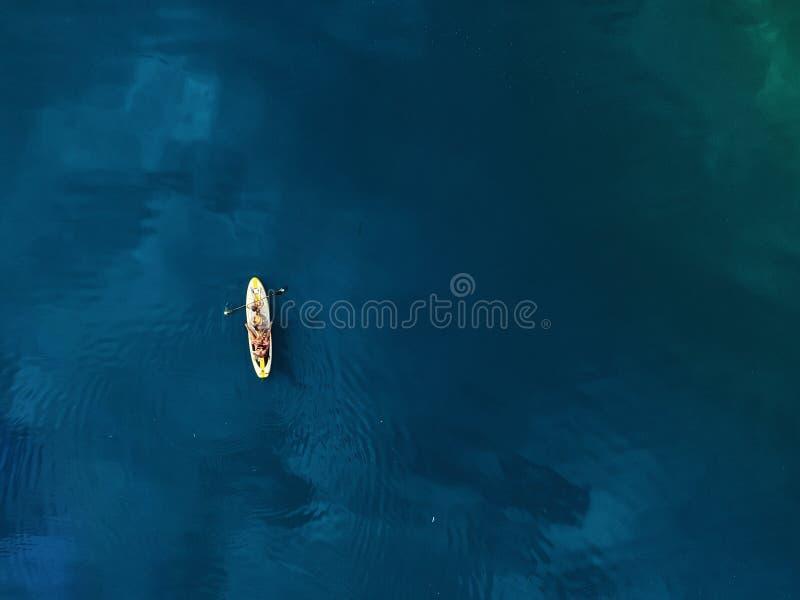 SUP立起桨充气冲浪板上家庭游乐的无人机视景 有孩子的母亲喜欢坐着 免版税库存照片