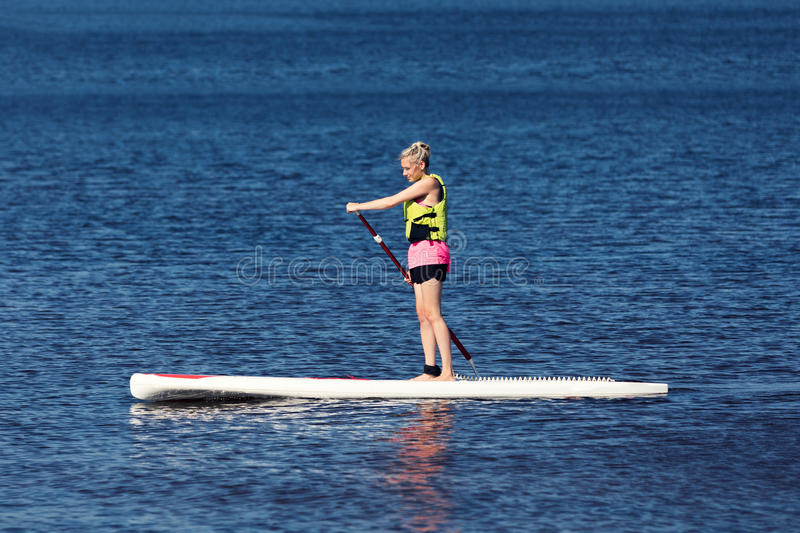 SUP fitness - woman on paddle board in the lake stock image