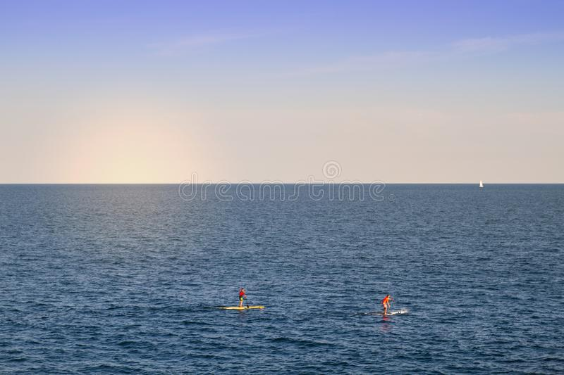 Sup riders at sunset stock photos