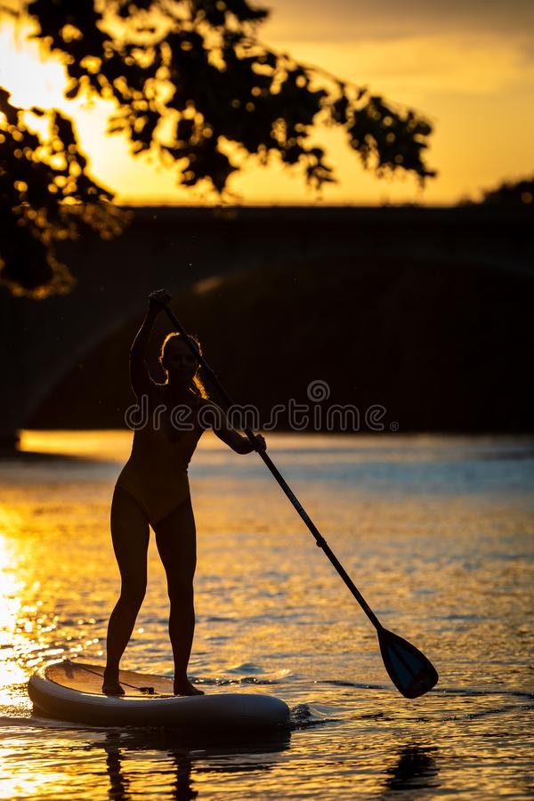 Pretty, young woman paddle boarding stock photography
