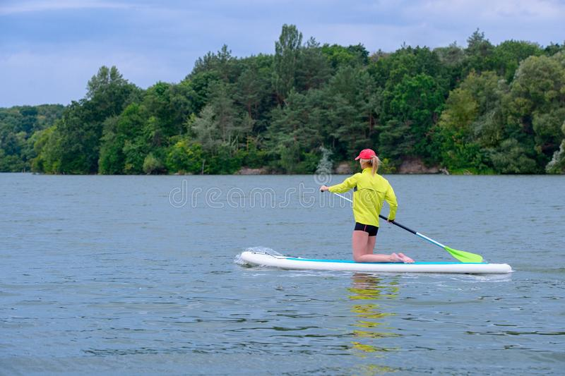 SUP Stand up paddle board concept - Pretty, young woman paddle boarding on a  lake stock image