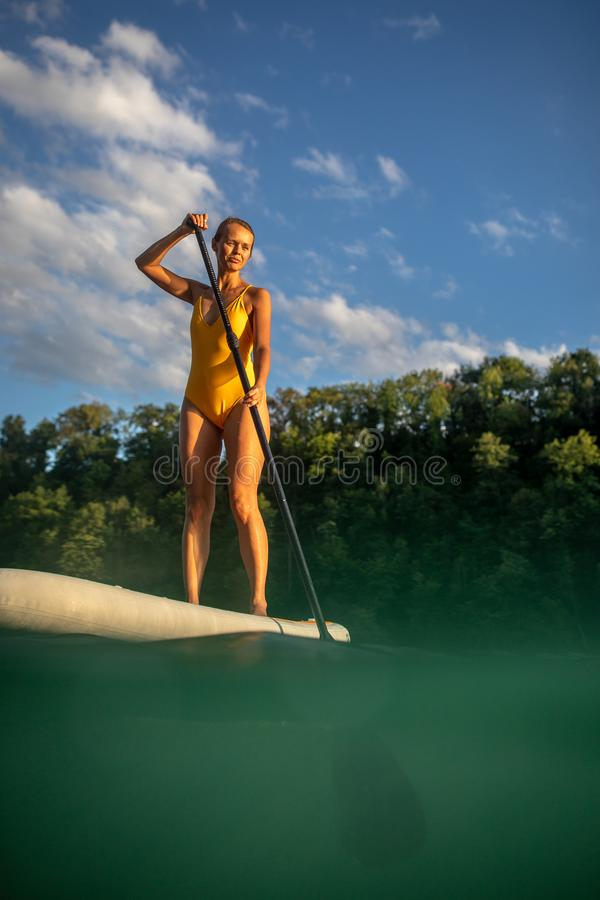Pretty, young woman paddle boarding royalty free stock images