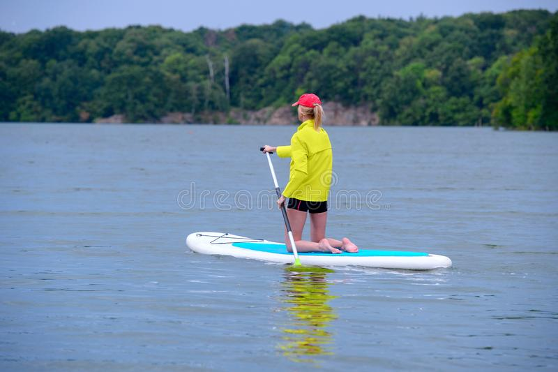 SUP Stand up paddle board concept - young woman paddle boarding on a lake royalty free stock photo