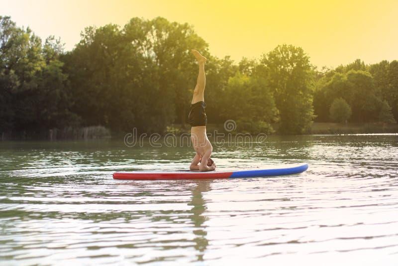 SUP yogatribune die omhoog headstand paddelen stock fotografie