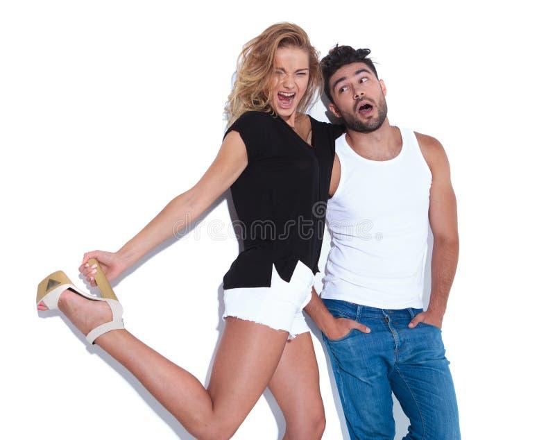 Super aufgeregte Frau zieht Mann ` s Haare und hält ihre Ferse stockfotos