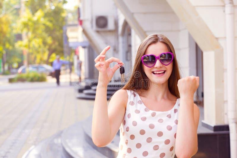 Super aufgeregtes lächelndes Mädchen, welches das Zeigen von Schlüsseln zu ihrem neuen Haus hält lizenzfreie stockfotos