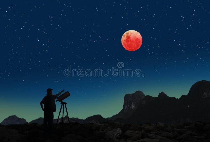 Super blue blood moon eclipse and a man with telescope. Picture of the Super blue blood moon eclipse on January 31, 2018 a phenomenon that happens only in so stock images