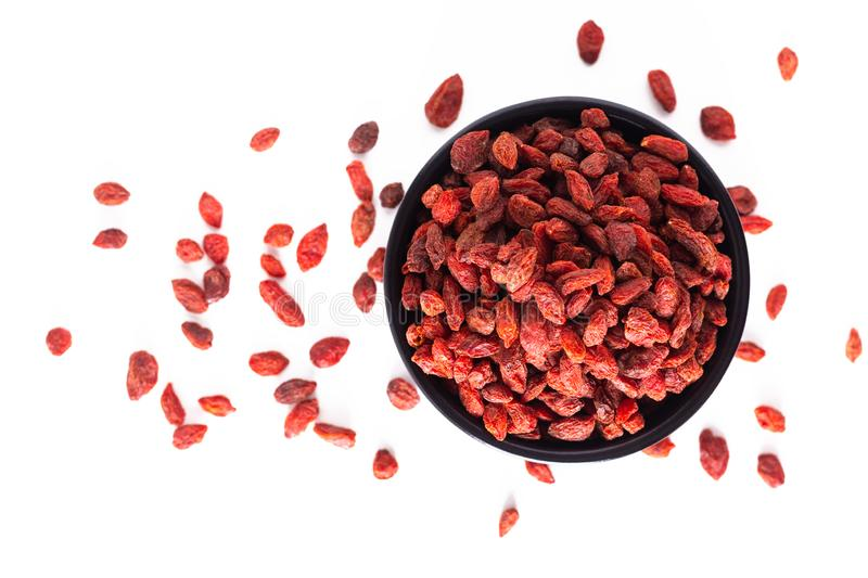 Super brain food dry Goji berry in black ceramic cup isolated on white background with copy space royalty free stock photography
