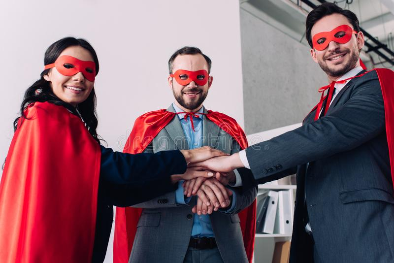super businesspeople in masks and capes putting hands together stock photography