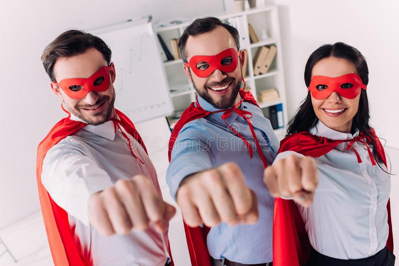 super businesspeople in masks and capes showing fists royalty free stock photography