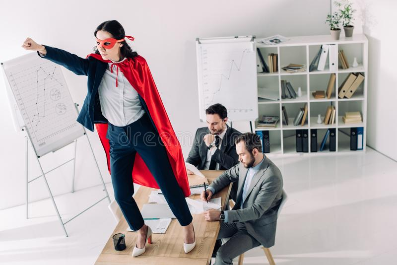 super businesswoman in mask and cape standing on table with hand up stock photo