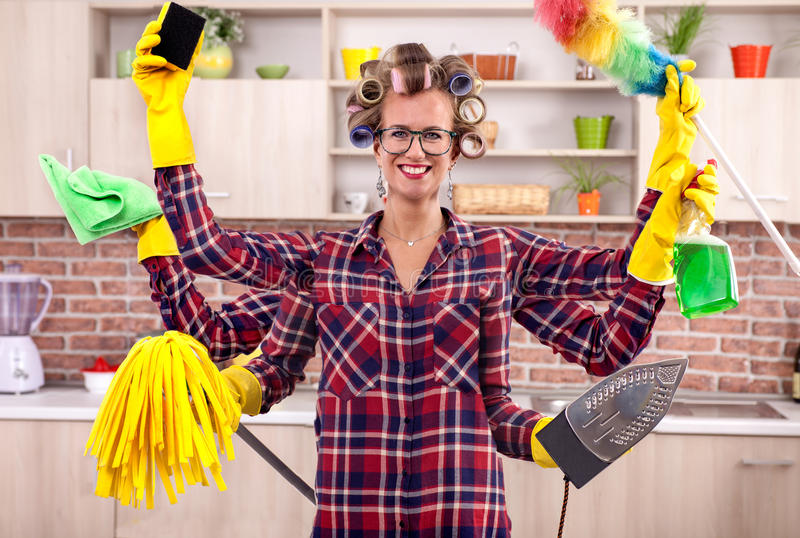 Super busy young housewife with six hands multitasking cleaning stock photography