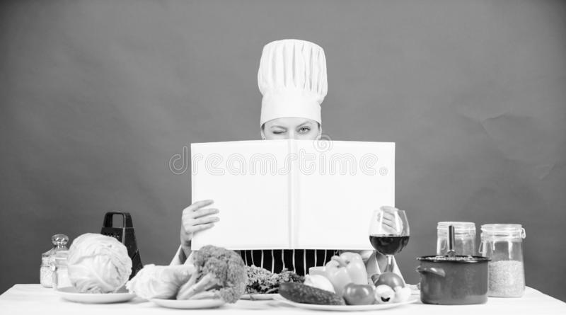 She is a super cook. Lady cook looking for cooking recipe in cookbook. Pretty woman reading cook book in kitchen. Cute. Cook housekeeper at kitchen table, copy stock photos