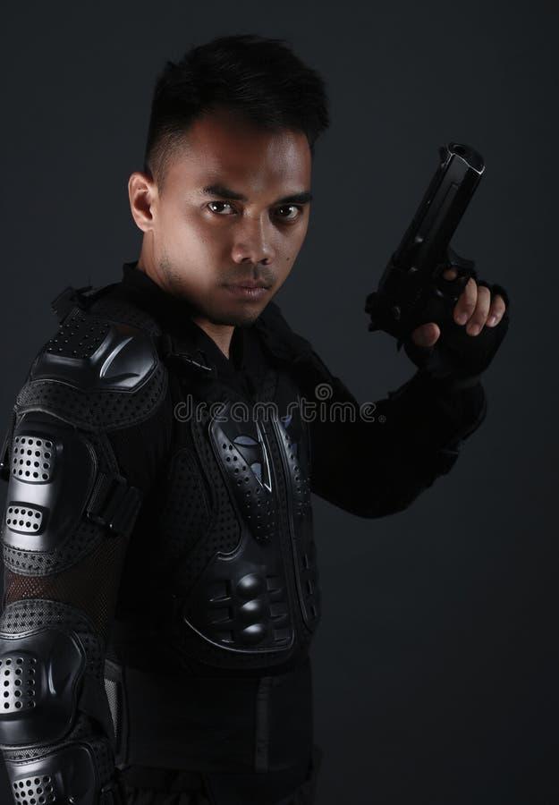 Super Cops- Knappe Aziatische mens die een kanon houden stock fotografie