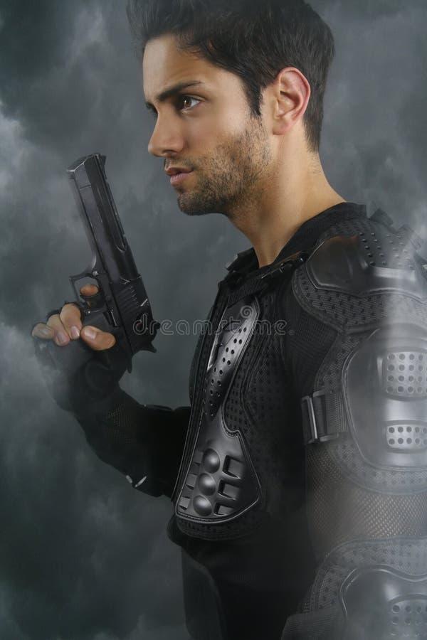 Super cops- knappe bruine mens die een kanon houden stock foto