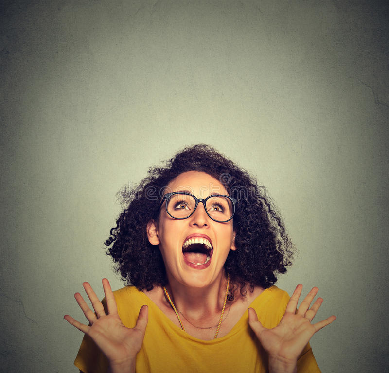 Super excited funky girl looking up. Isolated on grey wall background stock images
